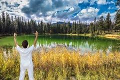 中年妇女,打扮为瑜伽,在小湖 库存照片