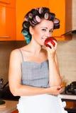 中年妇女主妇在厨房里用苹果 免版税库存照片