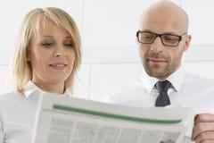中间成人企业夫妇读书报纸在厨房里 免版税库存图片