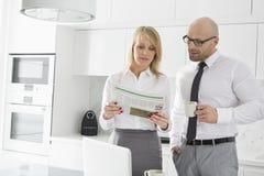 中间成人企业夫妇读书报纸,当食用咖啡在厨房时 免版税库存图片
