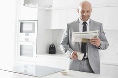 中间成人商人食用咖啡,当读报纸在厨房时 免版税库存照片