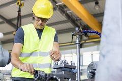 中间成人在金属工业的工作者运行的机械低角度视图  免版税库存照片