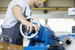 中间成人在金属工业的工作者运行的机械低角度视图  免版税图库摄影