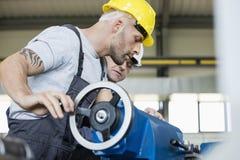 中间成人工作者侧视图有同事运行的机械的在产业 免版税库存图片