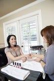 中间成人美丽的愉快的女性修指甲师擦亮的钉子  免版税库存图片