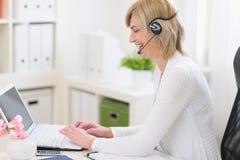 中年有耳机的女商人在工作 库存照片