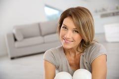 中年白肤金发的妇女在家 库存照片