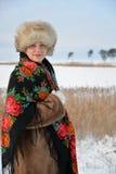 中年的妇女的画象在毛皮盖帽和一件五颜六色的披肩的花费反对冬天湖 免版税库存图片