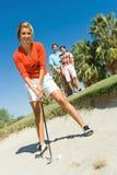 击中从砂槽的女性高尔夫球运动员球 免版税库存照片