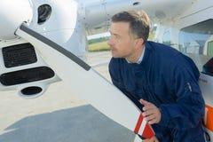 中间年龄工作为准备航空器的服务工程师 免版税库存图片