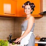 中间年龄美丽的妇女在有刀子的厨房里 免版税库存图片