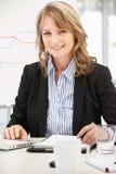 中间年龄女实业家在工作 免版税库存图片