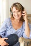 中间年龄妇女佩带的耳机 免版税库存照片