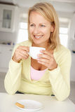 中间年龄妇女用咖啡在家 库存照片