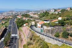 丰沙尔和高速公路,反对马德拉岛海岛山的修造鸟瞰图  免版税图库摄影