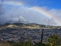 丰沙尔是马德拉岛的海岛的资本 当薄雾下来山,这条彩虹出现 库存图片