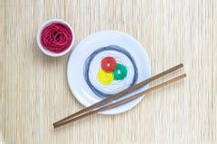 串用不同的颜色以寿司卷和酱油的形式用棍子在米黄竹席子minimalistic抽象概念 免版税库存图片