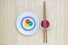 串用不同的颜色以寿司卷和酱油的形式用棍子在米黄竹席子minimalistic抽象概念 免版税库存照片