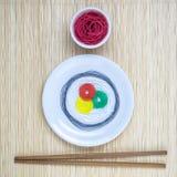 串用不同的颜色以寿司卷和酱油的形式用棍子在米黄竹席子minimalistic抽象概念 库存照片