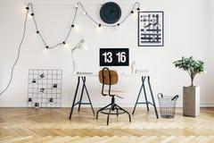 串起与电灯泡的光在时髦的工作区内部的白色墙壁上有人字形木条地板地板的一名学生的 实际照片 免版税库存照片