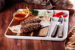 串起肉,牛肉,用凉拌卷心菜,蕃茄,在委员会的调味汁,纸,板材,叉子,刀子,菜单 免版税图库摄影