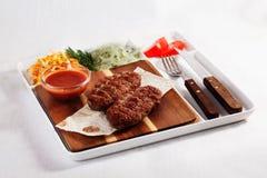 串起肉,牛肉,用凉拌卷心菜,蕃茄,在委员会的调味汁,纸,板材,叉子,刀子,被隔绝,菜单 图库摄影