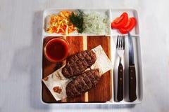 串起肉,牛肉,用凉拌卷心菜,蕃茄,在委员会的调味汁,纸,板材,叉子,刀子,被隔绝,菜单 库存图片