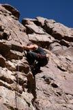 临近岩石顶层的登山人 免版税库存图片