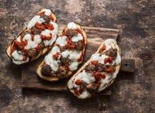 丸子、西红柿酱、无盐干酪和芝麻菜热的三明治在一个土气切板在一张木桌上,顶视图 可口锡 库存图片