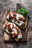 丸子、西红柿酱、无盐干酪和芝麻菜热的三明治在一个土气切板在一张木桌上,顶视图 可口锡 图库摄影