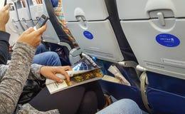 丹佛,科罗拉多,美国, 2017年12月30日-使用在她的智能手机的一个少妇团结的App和拿着半球杂志 econ 库存照片