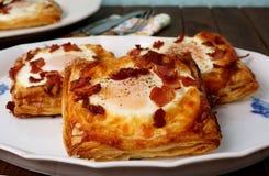 丹麦酥皮点心、早餐用鸡蛋,烟肉、乳酪和油酥点心 免版税图库摄影