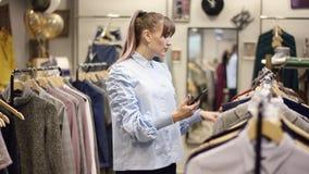 为一件夹克和一件礼服照相在智能手机照相机的俏丽的妇女在衣物商店,当选择衣裳时 股票视频
