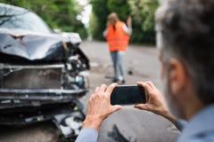 为一辆残破的汽车照相的无法认出的人在事故以后 库存图片