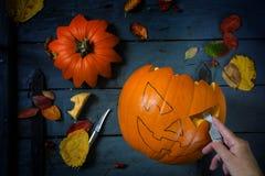 为万圣夜雕刻一个南瓜或在蓝色rusti的秋天装饰 库存图片