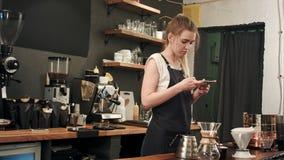 为与智能手机的女性barista准备的cofee照相 免版税库存照片