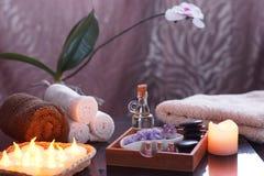 为与电灼烧的蜡烛和特里毛巾的温泉治疗设置 在一块木箱、油和石头按摩的 库存图片