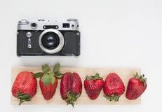 为与老照相机的艺术品和在白色背景的红色草莓嘲笑  顶视图 安置文本 免版税库存图片