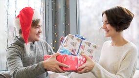 为交换礼物的夫妇关闭,当一起时庆祝圣诞节和新年 圣诞老人项目的帽子和妇女人 免版税库存图片