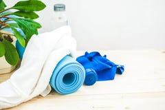 为体育、瑜伽席子、毛巾和一个瓶在轻的背景的水设置 一个健康生活方式地方的概念文本的 免版税库存图片