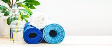 为体育、蓝色瑜伽席子毛巾和一个瓶在轻的背景的水设置一种健康生活方式的概念 复制空间禁令 库存照片