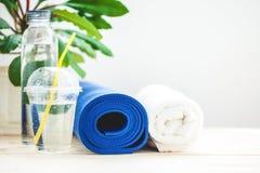 为体育、蓝色瑜伽席子毛巾和一个瓶在轻的背景的水设置一种健康生活方式的概念 复制空间 免版税库存图片