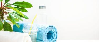 为体育设置 瑜伽席子毛巾和一个瓶在轻的背景的水一种健康生活方式的概念 复制空间横幅 库存照片