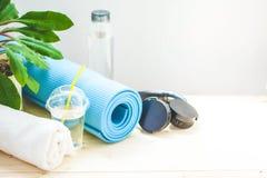 为体育设置 蓝色瑜伽席子毛巾耳机和一个瓶在一种健康生活方式的概念复制的轻的背景的水 免版税库存照片