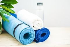 为体育,瑜伽席子,毛巾,一个瓶在轻的背景的水设置 一种健康生活方式的概念 复制空间 库存照片