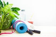 为体育,瑜伽席子,毛巾,圆滑的人跳绳,一个瓶水设置 健康生活方式拷贝空间的概念 免版税库存照片