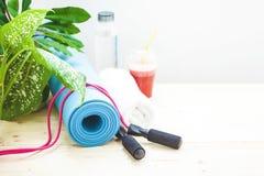 为体育,瑜伽席子,毛巾,圆滑的人,跳绳,一个瓶水设置健康生活方式拷贝空间的概念 图库摄影