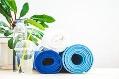 为体育,蓝色瑜伽席子毛巾设置,并且一个瓶在一个健康生活方式拷贝的概念间隔的轻的背景的水 图库摄影