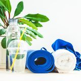 为体育,蓝色瑜伽席子毛巾设置,并且一个瓶在一个健康生活方式拷贝的概念间隔的轻的背景的水 库存图片