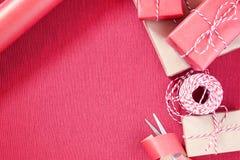 为假日做准备-礼品包装材料在红色和米黄包装纸 免版税库存图片